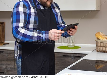 A Man In The Kitchen Is Watching A Recipe For Cooking A Dish On A Tablet On The Internet, Background