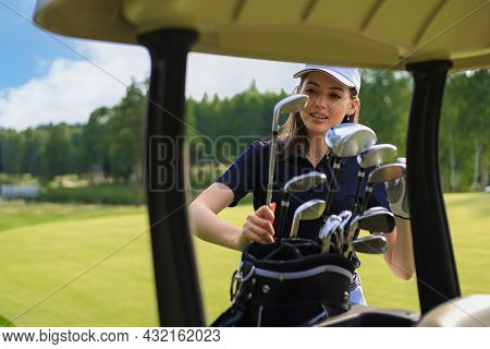 Professional Woman Golf Player Choosing The Golf Club From The Bag.
