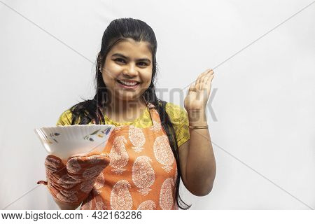 A Pretty Indian Housewife Woman Wearing Cooking Apron And Oven Gloves With A Serving Bowl In Hand Sm