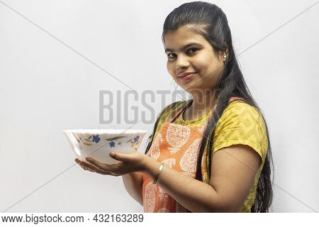 A Pretty Indian Housewife Woman In Cooking Apron Holding A Serving Bowl In Hand Smiles On White Back