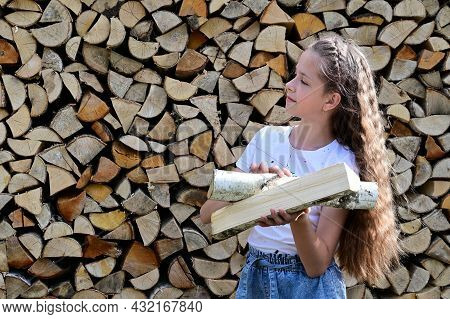 Beautiful Girl With Long Hair In White T-shirt On Background Of Pile Of Firewood. Concept Of Harvest