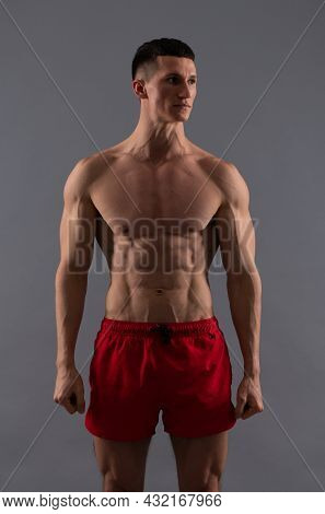 He Is In Good Shape. Shirtless Guy In Sports Shorts. Fit Guy Grey Background. Sporting Man