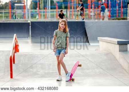 Pretty preteen girl with skateboard outdoors. Female skater child close to the park riding ramp