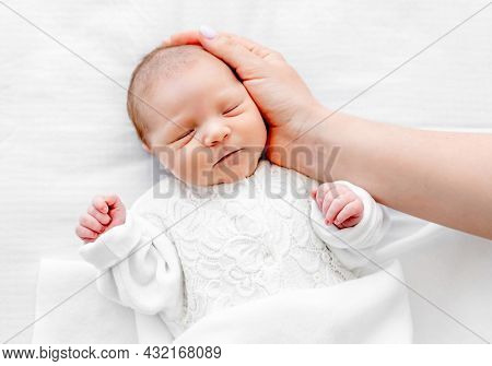Adorable newborn baby girl wearing white costume lying in the bed, sleeping and her mother hand cares about her. Portrait of cute napping infant child and parent love