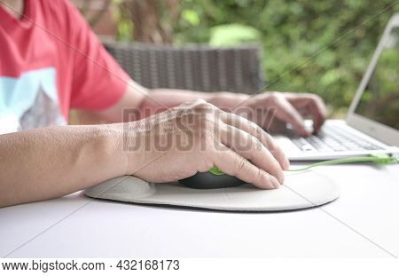 Man's Fingers Clicking On Mouse, Resting His Wrist On Wrist Rest.  Close Up Shot.