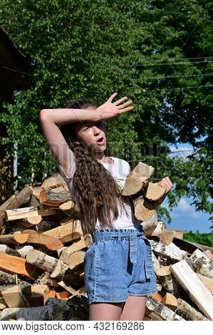 Beautiful Tired Girl With Long Hair In White Shirt Puts Firewood In Pile. Concept Of Harvesting Fire