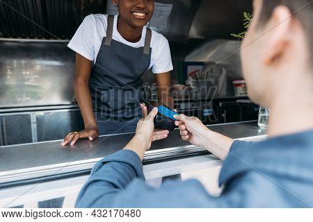 Smiling Salesman Giving Packages With Street Food To A Female Customer. Food Truck Owner Serves The