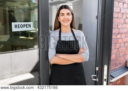 small business, reopening and service concept - happy smiling woman with reopen banner on window or door glass