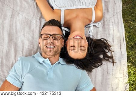 leisure, vacation and people concept - happy couple lying on picnic blanket