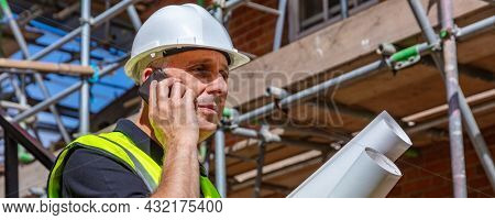 Male builder foreman, worker or architect on construction site holding building plans and talking on his cell phone panoramic web banner header