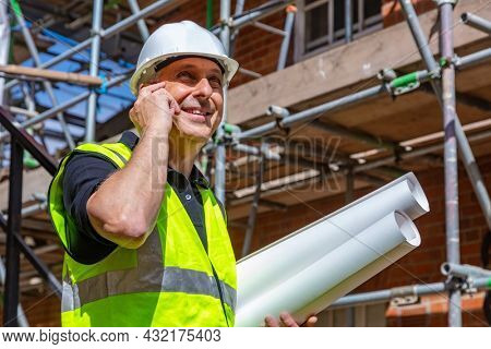 Male builder foreman, worker or architect on construction site, happy, smiling, holding building plans and talking on his cell phone