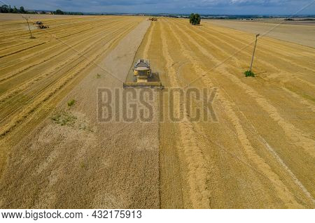Yellow Combine Harvesters On A Golden Wheat Field Harvest Wheat. Photo From A Drone. Aerial View. Ex