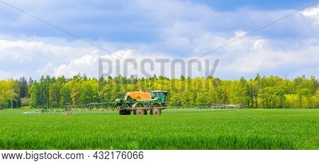 Tractor Sprayer Treats Millet In The Field With Fertilizers. Pest Protection.