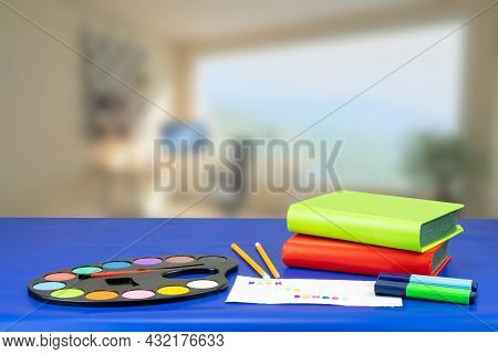 Colorful School Equipment And Two Book On Dark Blue Table Against Abstract Blurred Office Background