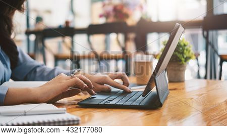 Close Up Of Student Girl Hands Comparing Notes On Digital Tablet Sitting On A Desk. Female Using Tab