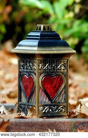 A Grave Lantern With Red Hearts Of Glass On A Gravestone Against Autumn Leaves In A Blurred Backgrou