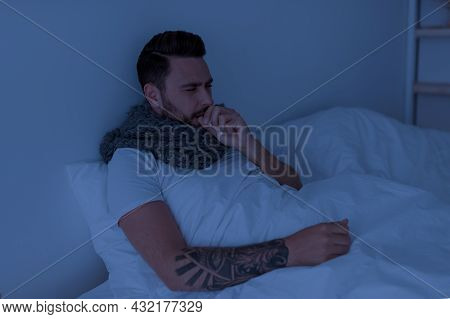 Coronavirus, Influenza Concept. Sick Young Man Coughing, Holding Paper Napkin Near Mouth, Sitting In