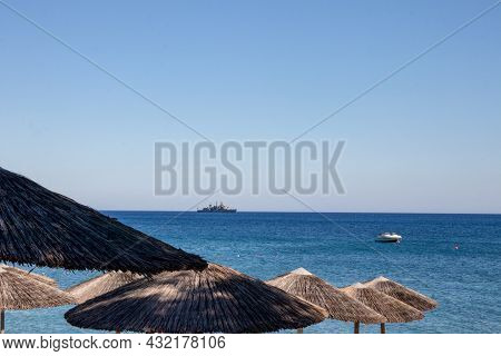 Summer Backdrop. Closeup On A Brown Straw Umbrella Or Beach Parasol Against Blurred Blue Sea And Sky