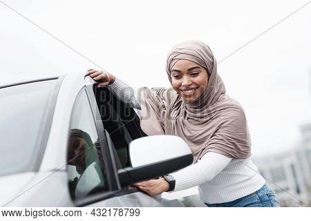Satisfied Cute Islamic African American Lady Customer In Hijab Touching New Car Outdoor, Enjoying Bu