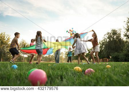 Group Of Children And Teachers Playing With Rainbow Playground Parachute On Green Grass, Low Angle V