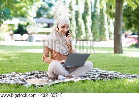 Cheerful Young Arabian Muslim Woman In Hijab Uses Laptop And Smartphone To Communicate With Client