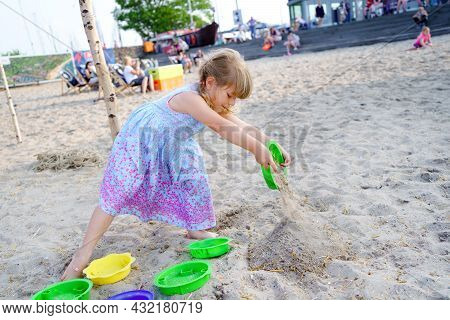 Little Preschool Girl Playing With Sand Toys On The Beach. Cute Happy Toddler Child On Family Vacati