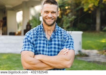 Portrait of smiling caucasian man outside house looking at camera in garden. spending time at home.