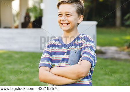 Smiling caucasian boy outside house looking away from camera in garden. spending time at home.