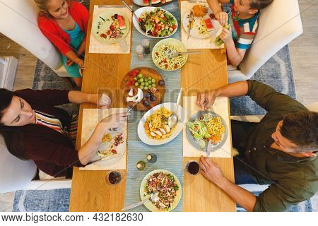 Overhead view of caucasian parents with son and daughter sitting at table and having dinner. family spending time together at home.