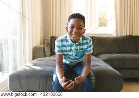 Portrait of smiling african american boy using smartphone and sitting on couch in sunny living room. spending time alone at home.