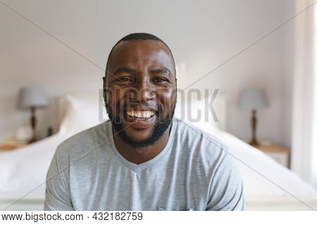 Portrait of happy african american man looking at camera and smiling in bedroom. spending time alone at home.