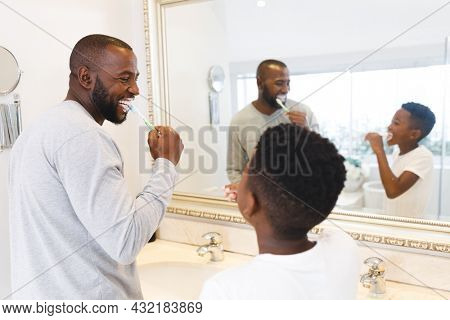 Smiling african american father and son having fun brushing teeth together in bathroom. family spending time at home.