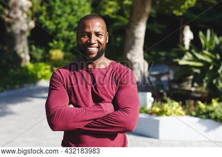 Portrait of african american man with arms crossed smiling and looking at camera in sunny garden. spending time alone at home.
