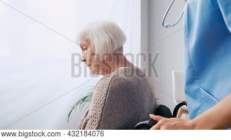 Geriatric Nurse With Stethoscope Moving Aged Woman In Wheelchair