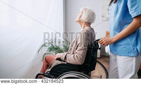 Geriatric Nurse Moving Aged Woman In Wheelchair
