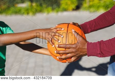 Midsection of african american father and son holding basketball together in garden. family spending time at home.