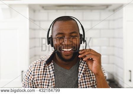 Smiling african american man sitting at countertop in kitchen making video call using headset. remote working from home with technology.