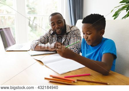 Smiling african american father and son sitting at table in dining room, working and doing homework. family spending time at home.