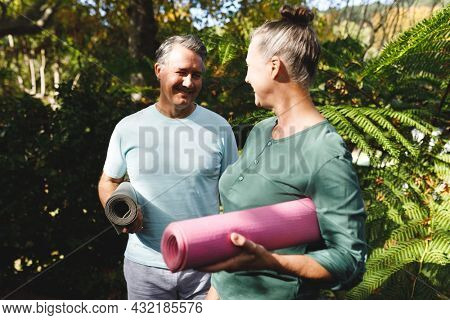 Happy senior caucasian couple practicing yoga, holding yoga mats in sunny garden. healthy retirement lifestyle, spending time at home.