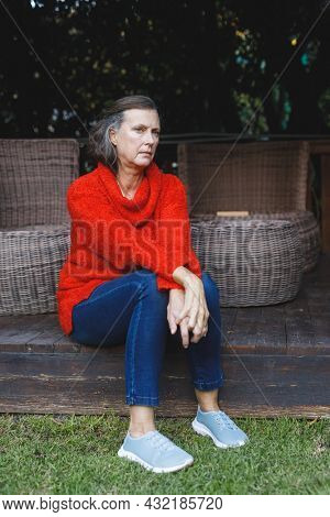 Thoughtful senior caucasian woman sitting and looking away in garden. retirement lifestyle, spending time alone at home.