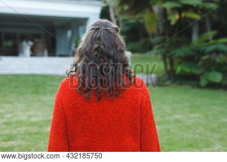 Rear view of senior caucasian woman walking in her garden. retirement lifestyle, spending time at home.