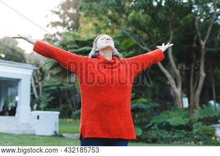 Happy senior caucasian woman with arms outstretched in garden. healthy retirement lifestyle, spending time self caring at home.