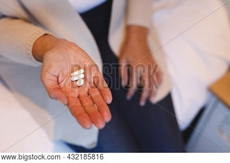 Mid section of senior caucasian woman in bedroom sitting on bed, holding pills. retirement lifestyle, illness and the aging process