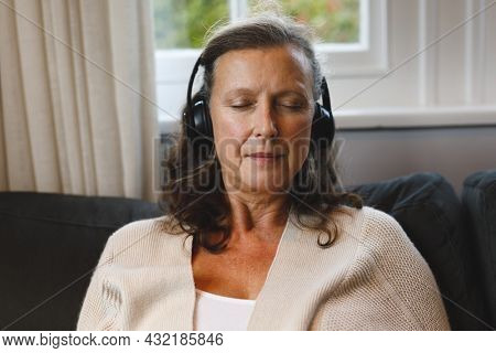 Happy senior caucasian woman in living room sitting on sofa, wearing headphones. retirement lifestyle, spending time alone at home with technology.