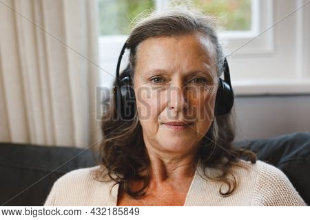 Portrait of happy senior caucasian woman in living room sitting on sofa, wearing headphones. retirement lifestyle, spending time alone at home with technology.