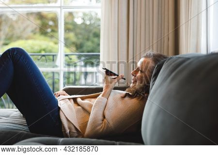 Happy senior caucasian woman in living room sitting on sofa, talking on smartphone. retirement lifestyle, spending time alone at home with technology.