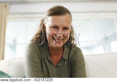 Smiling senior caucasian woman in living room, sitting on sofa, making video call. retirement lifestyle, spending time at home with technology.