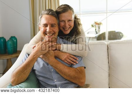 Portrait of happy senior caucasian couple in living room, sitting on sofa, embracing. retirement lifestyle, spending time at home.