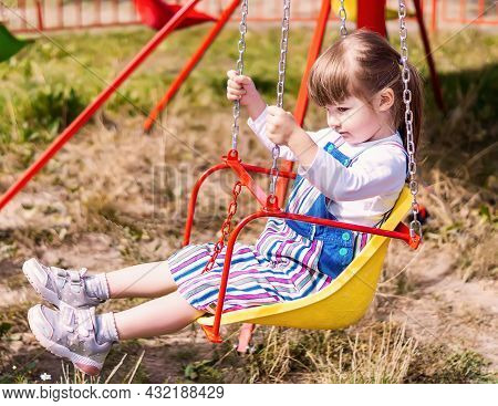 A Little Girl Is Having Fun On A Chain Carousel. A Cute Little Girl Is Riding On A Swing. A Beautifu