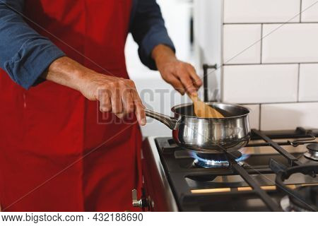 Midsection of senior caucasian man wearing apron in kitchen cooking. retirement lifestyle, spending time at home.
